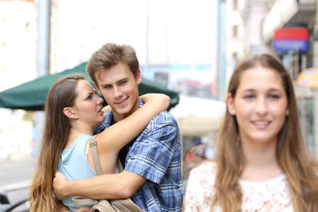 Unfaithful man hugging his girlfriend while is looking another one in the street