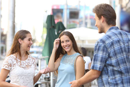 love at first sight: Candid girl with a friend flirting with a boy in the street Stock Photo