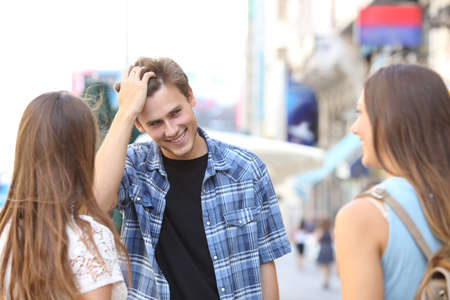 Handsome young man flirting with two girls in the street