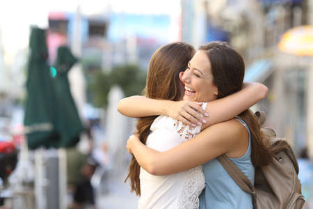girl friends: Happy meeting of two friends hugging in the street