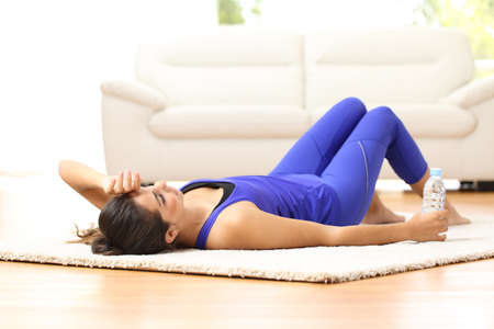 tired person: Tired sportswoman lying on the floor at home after sport