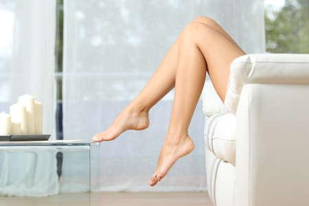 nackt: Profil eines perfekten Frau, die Beine auf der Couch zu Hause Haarentfernung Konzept sitzend