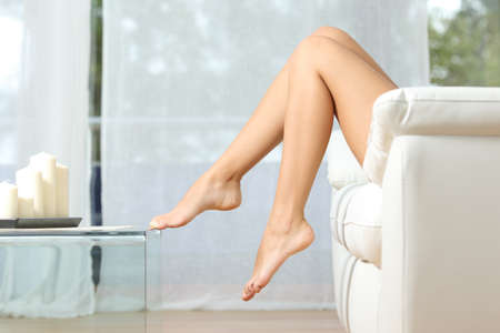 naked: Profile of a perfect woman legs sitting on a couch at home hair removal concept