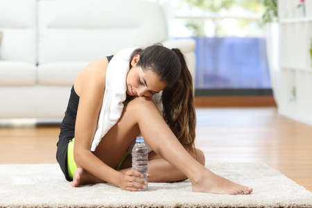Tired fitness woman resting and thinking sitting on the floor after sport at home