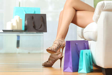 Fashion shopper legs with shopping bags sitting on a couch at home Stock Photo