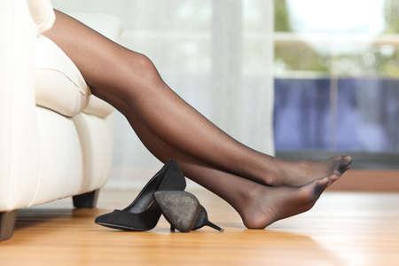 pies bonitos: Perfil de un cansadas piernas de mujer con medias de nylon negro descansando en el sofá en casa después del trabajo