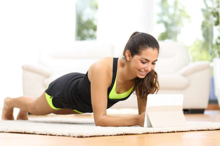 the calories: Fitness woman exercising on the floor at home and watching fitness videos in a tablet