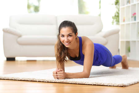 smiling lady: Fitness woman exercising on the floor at home and looking to the camera