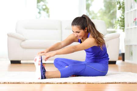 Fitness žena protažení nohou sedí na podlaze doma