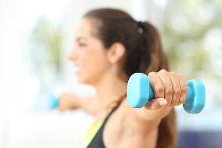weight room: Close up of a fitness woman hand doing weights at home