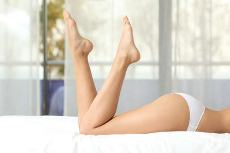 nude young girl: Profile of a perfect woman waxed legs lying on a bed at home