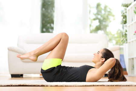 woman working out: Fitness girl doing crunches lying on the floor at home Stock Photo