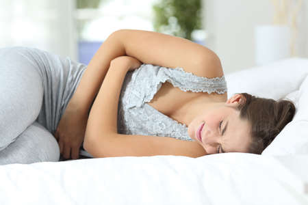 stomach: Girl suffering menstrual pains lying on the bed at home