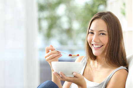 Casual happy woman dieting and eating cornflakes sitting on a couch at home Standard-Bild
