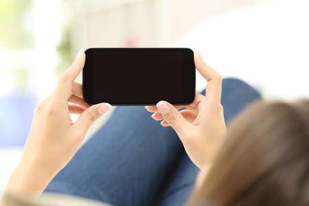 viendo television: Vista posterior de un primer plano de manos de una mujer que miran medios de comunicaci�n en un tel�fono inteligente acostado en un sof� en casa