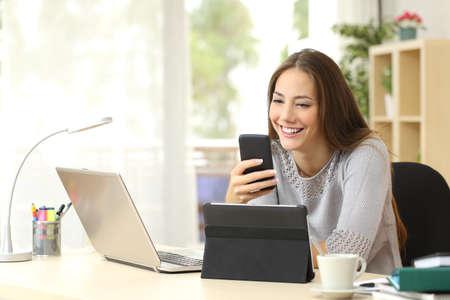 vrouwen: Gelukkig vrouw die werkt met behulp van meerdere apparaten op een bureau thuis