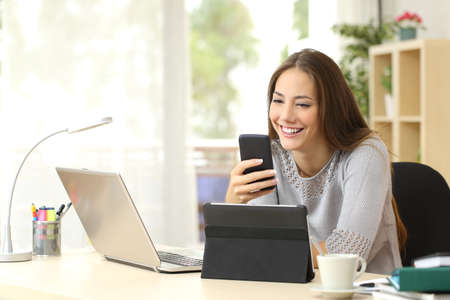 medios de comunicaci�n social: Mujer feliz que trabaja el uso de m�ltiples dispositivos en un escritorio en casa