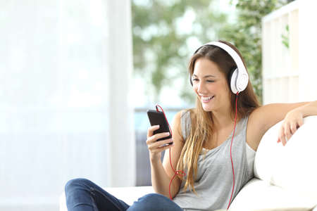 listening device: Happy girl listening to music from mobile phone sitting on a couch at home Stock Photo