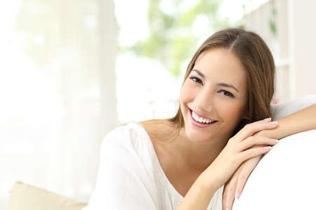 美女: 美的女人有白色完美的微笑在家裡看著相機