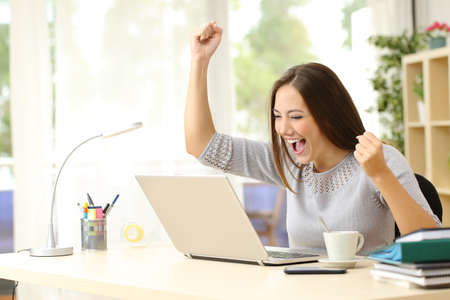 gente exitosa: ganador eufórico viendo un ordenador portátil en un escritorio ganar en casa