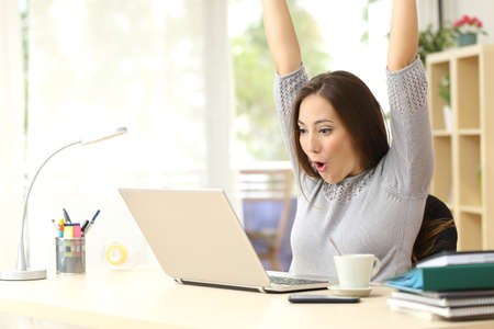 successful business: Euphoric and surprised winner winning online watching a laptop at home