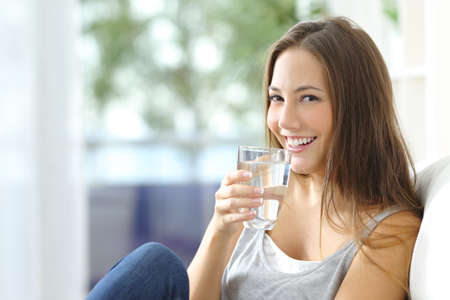 alimentacion: Agua Muchacha sentada en un sofá en casa bebiendo y mirando a cámara