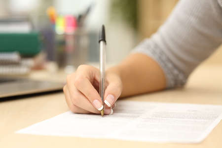 business  deal: Close up of a woman hand writing or signing in a document on a desk at home or office Stock Photo