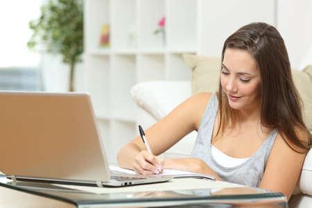jeune fille: Entrepreneur ou �tudiants qui travaillent ou �tudient � la maison et d'�crire des notes assis sur le plancher � la maison