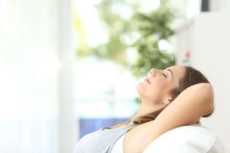 aire puro: Perfil de una mujer hermosa de relax tumbado en un sofá en casa