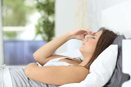 chory: Profil ból głowy Kobieta cierpi na leżącego na łóżku w domu