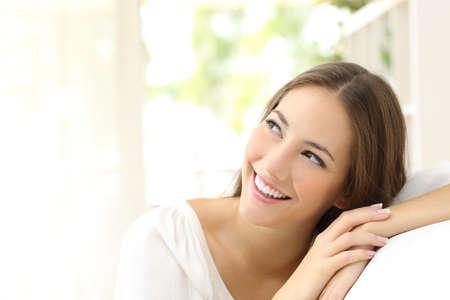 Krása věří, žena při pohledu z boku sedí na gauči doma Reklamní fotografie