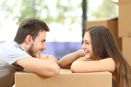 looking at each other: Profile of a happy couple moving house looking each other leaning on a box