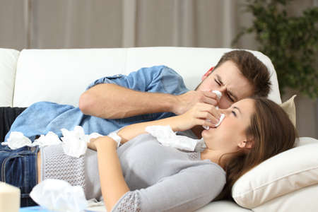 very cold: Ill couple sneezing in tissue lying on a couch at home. Flu concept Stock Photo