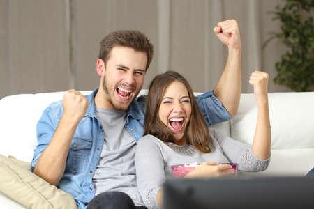 집에서 소파에 앉아 TV를보고 기쁘게 커플 스톡 콘텐츠
