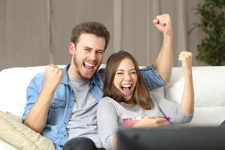 Euphoric couple watching tv sitting on a couch at home