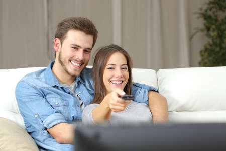livingroom: Happy couple using remote control to change channel on tv sitting on a couch at home