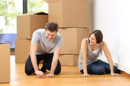 cinta de medir: Feliz pareja de mudarse de casa y tomar medidas en conjunto para los muebles
