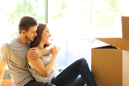 renovation property: Happy couple hugging moving new house sitting on the floor and looking through the window