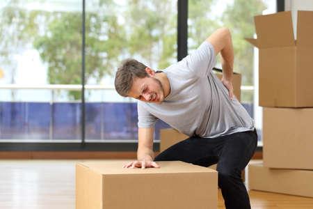 lesionado: El hombre sufre de dolor de espalda moviendo cajas en su nueva casa