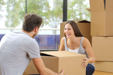 carrying girlfriend: Happy couple or marriage lifting boxes moving home Stock Photo