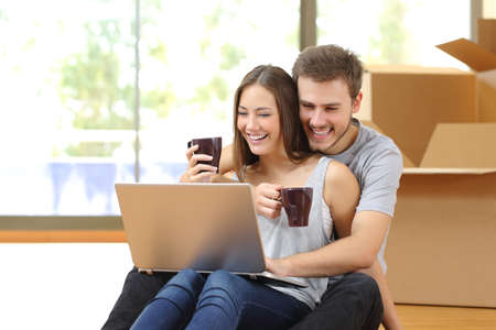 Couple buying online with a laptop and moving house sitting on the floor Foto de archivo