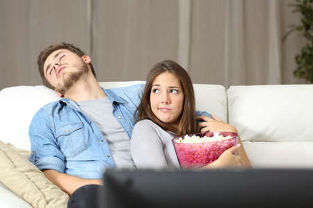 funny movies: Couple incompatibility problems watching tv sitting on a couch at home Stock Photo