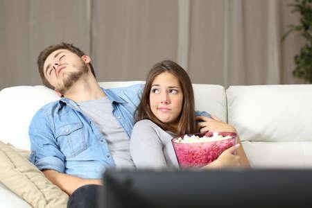 couple sleeping: Problemas de incompatibilidad pareja viendo la televisión sentado en un sofá en casa