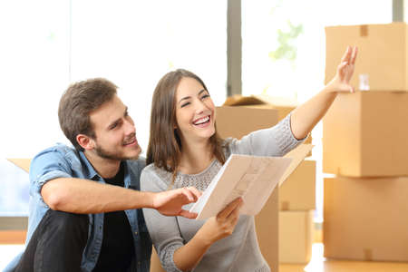 apartment interior: Happy couple planning decoration when moving home sitting on the floor