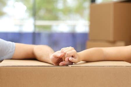 Close up de um casal segurando as mãos sobre uma caixa de cartão e mudar de casa Imagens