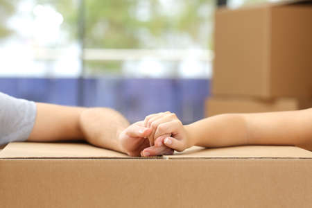 house moving: Close up of a couple holding hands over a carton box and moving home Stock Photo