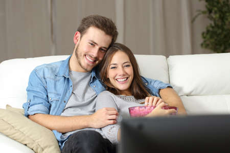 woman watching tv: Happy couple watching a movie on tv sitting on a couch at home