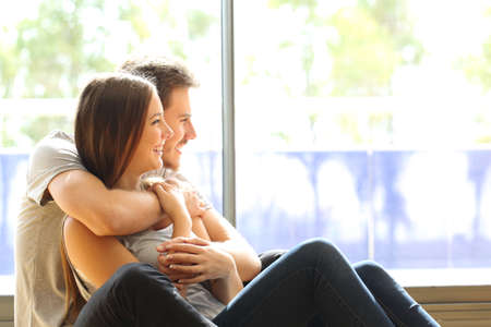 project planning: Couple or marriage in his new home looking through the window Stock Photo
