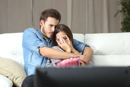 horror movies: Couple watching and enjoying terror tv movie sitting on a couch at home