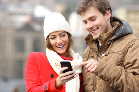 Happy couple consulting a smart phone in winter in the street